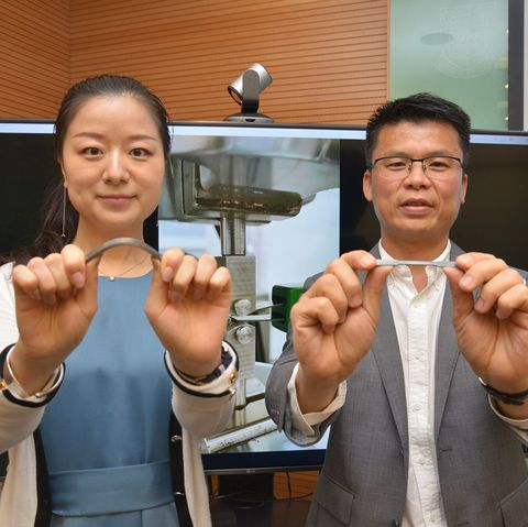 two scientists stand side by side, each holding up a sample of a silvery metal