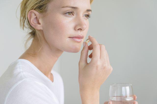 woman taking an omega 3 capsule