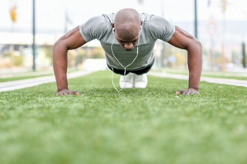 Surface Level View Of Man Doing Push-Ups On Grassy Field