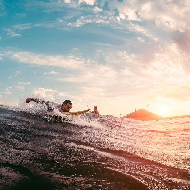 Surfer starting to ride a wave at sunset - Man surfin outdoor inside ocean- Extreme sport and vacation concept - Focus on male body