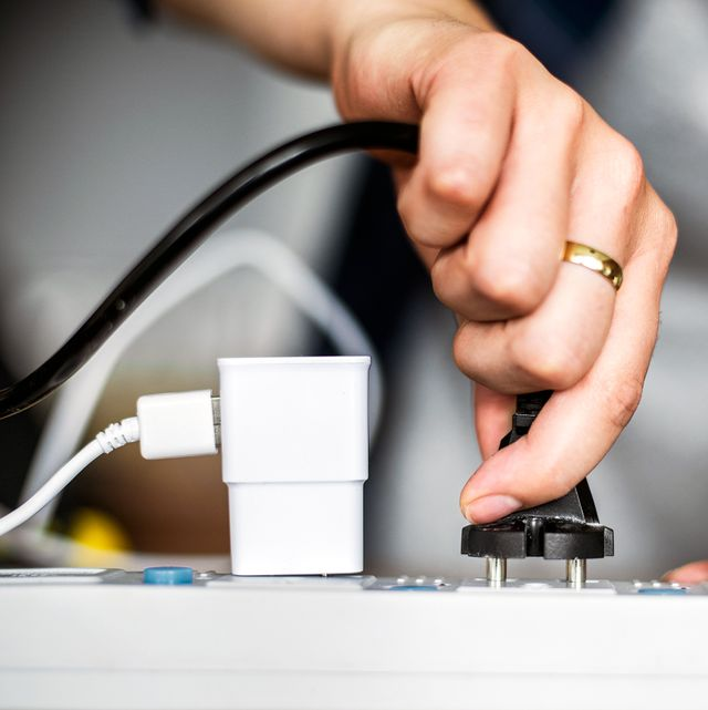 person plugging in cord to surge protector
