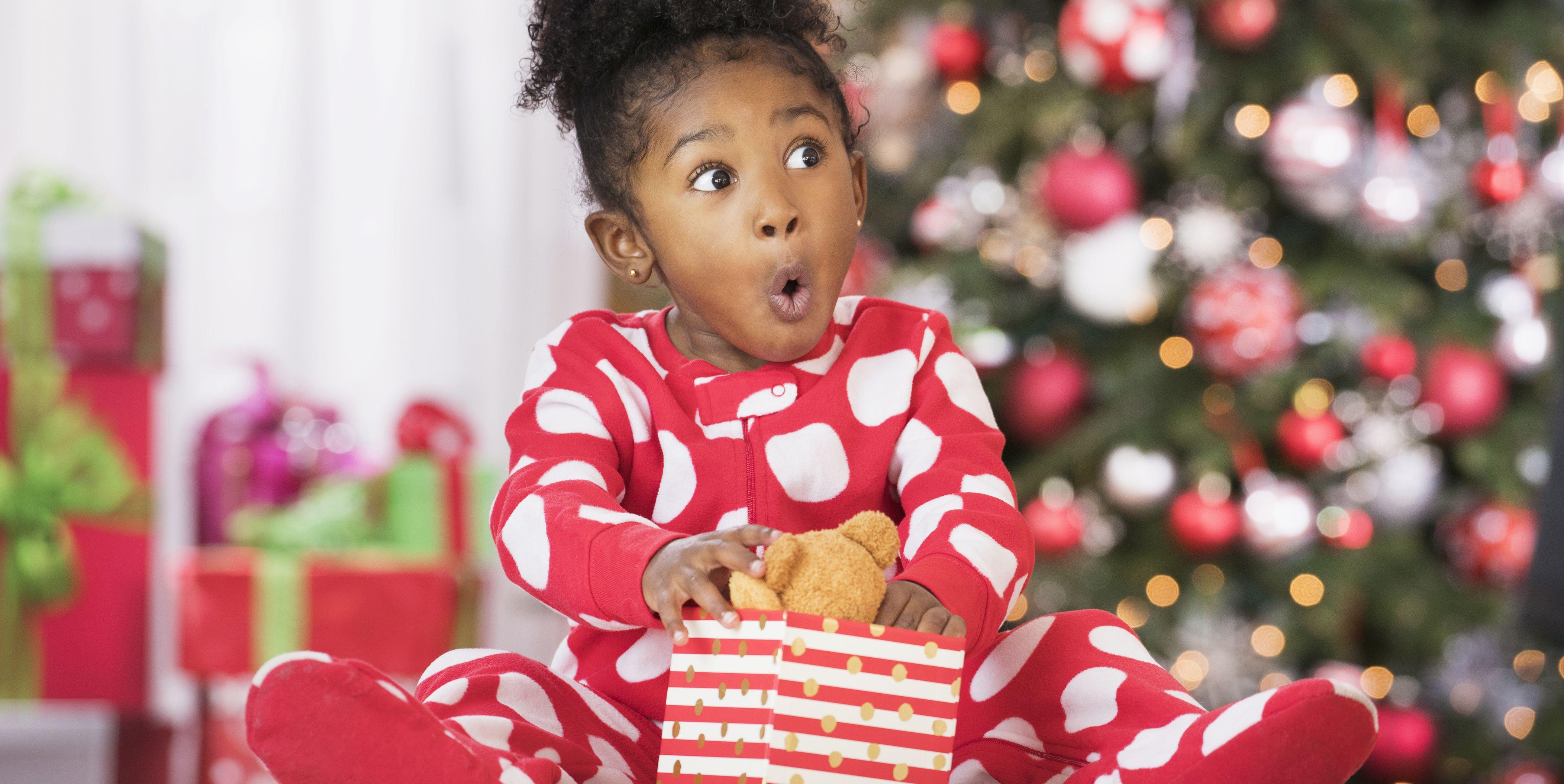 Niña abriendo regalo de Navidad