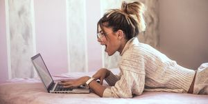 Surprised young woman lying on bed using laptop