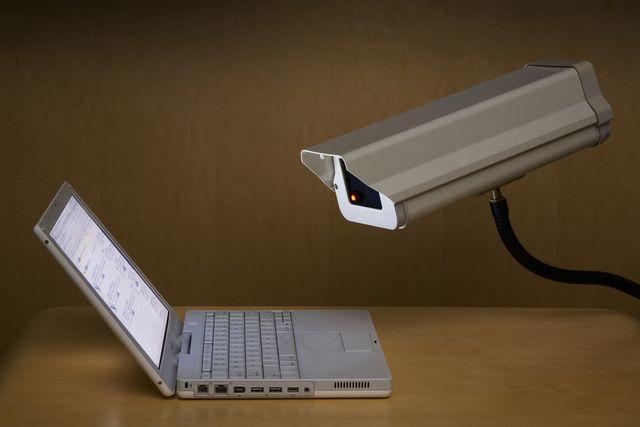 surveillance camera peering into laptop computer