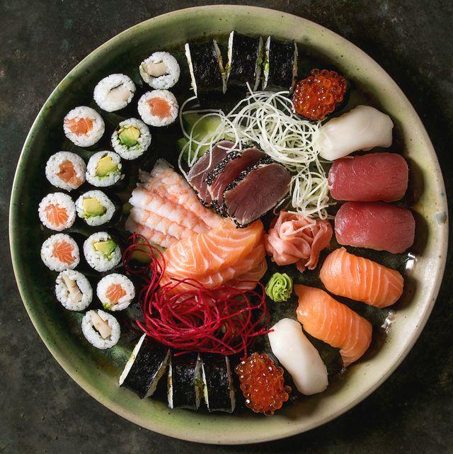sushi set nigiri sashimi and sushi rolls in ceramic serving plate
