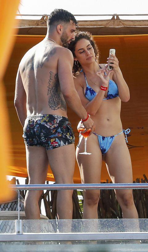 el colaborador y su chica, en bañador y bikini, consultan el móvil al borde de la piscina
