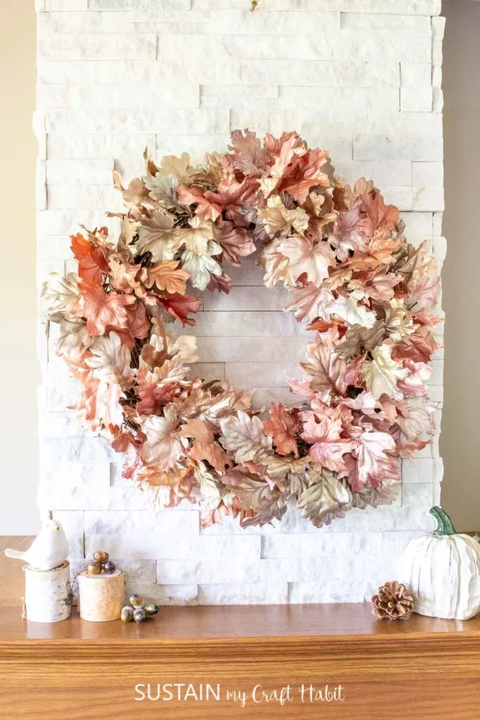 wreath with fall leaves painted metallic colors hanging on white brick