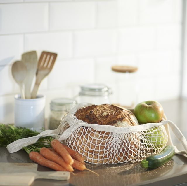 a selection of fresh organic produce in a plastic free reusable shopping bag on a zero waste kitchen worktop