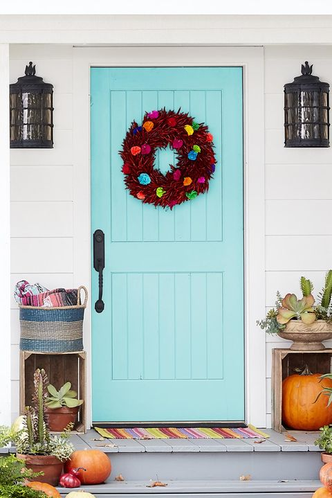 chili wreath with colorful paper flowers on a turquoise door