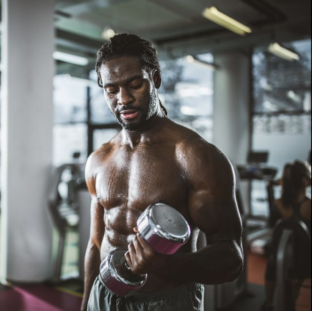 sweaty african american athlete exercising with dumbbell in a gym
