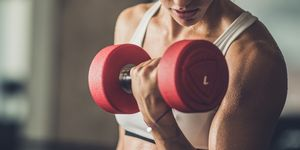 Sweaty athletic woman exercising with dumbbells in a health club.