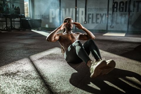Sweaty black athlete doing sit-ups in a gym.