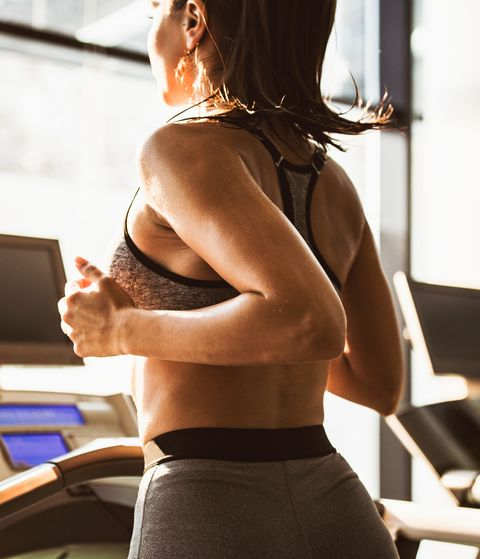 Sweaty female athlete running on treadmill during sports training in a health club.