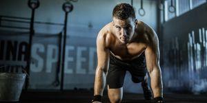 Sweaty male athlete having gym training in a gym.