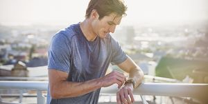 Sweaty male runner resting checking smart watch fitness tracker at sunny urban railing