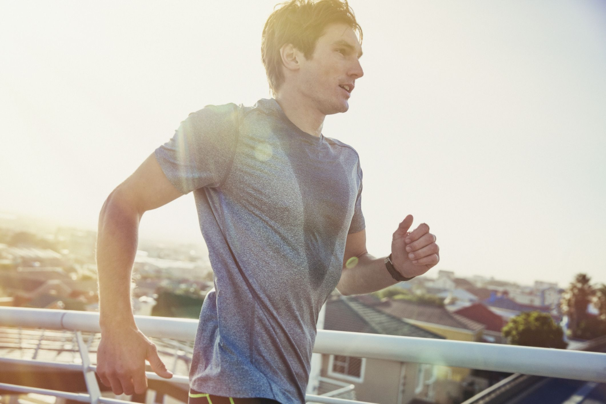 Sweaty male runner running on sunny urban footbridge at sunrise