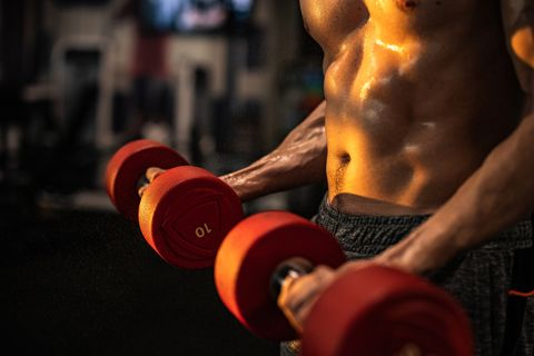 sweaty muscular build athlete exercising with dumbbells in a gym