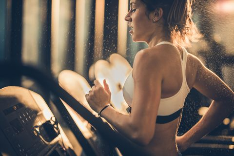 sweaty woman running on treadmill during sports training in a gym