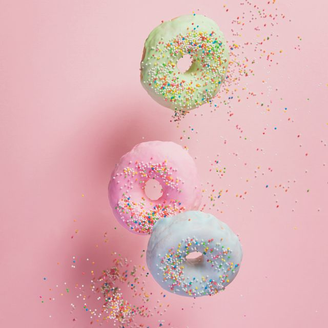sweet and colourful doughnuts with sprinkles falling or flying in motion