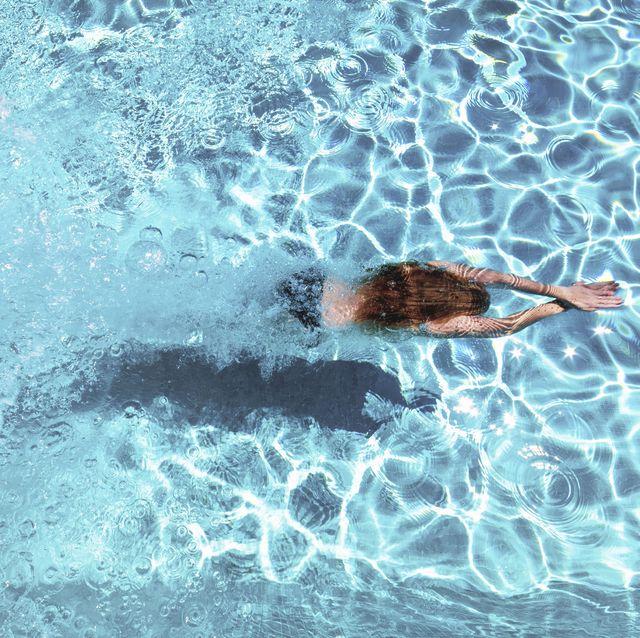 refreshing, woman diving underwater in swimming pool, southern spain