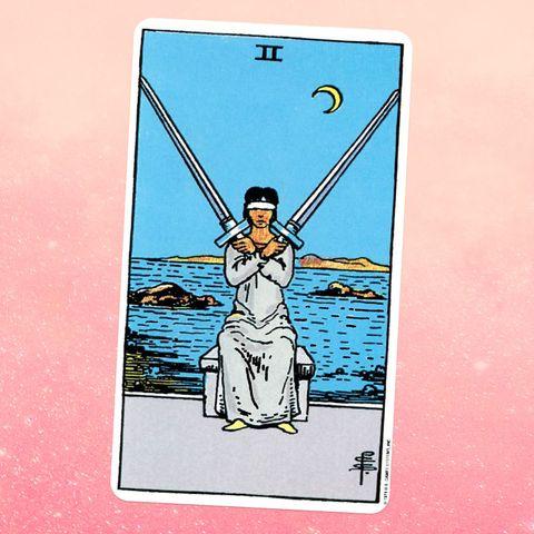 la carte de tarot les deux d'épées, montrant une personne aux yeux bandés dans une robe blanche tenant deux épées croisées devant eux
