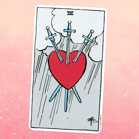 the tarot card the three of swords, showing a red heart stuck through with three swords, with a rainy sky behind it