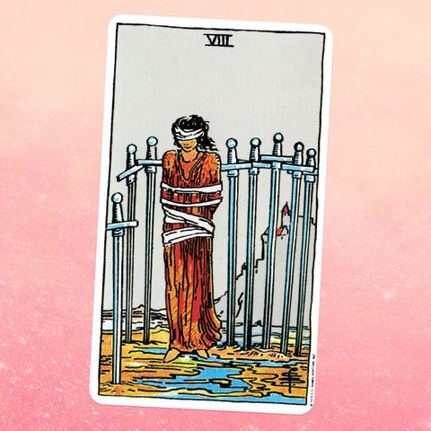 the tarot card the eight of swords, showing a person in a long robe, tied up and blindfolded, surrounded by eight swords