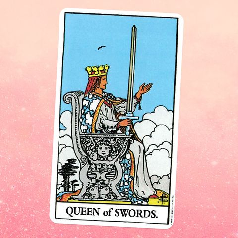 the tarot card for the queen of swords, showing the profile view of a white woman in a white robe, blue and white patterned cape, and gold crown sitting on a silver throne and holding a sword
