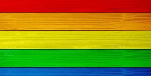Symbol color of LGBTQ+ on wooden wall background. red orange yellow green blue purple.