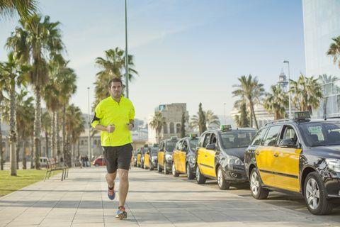 un hombre empieza a correr por la acera de una calle de barcelona