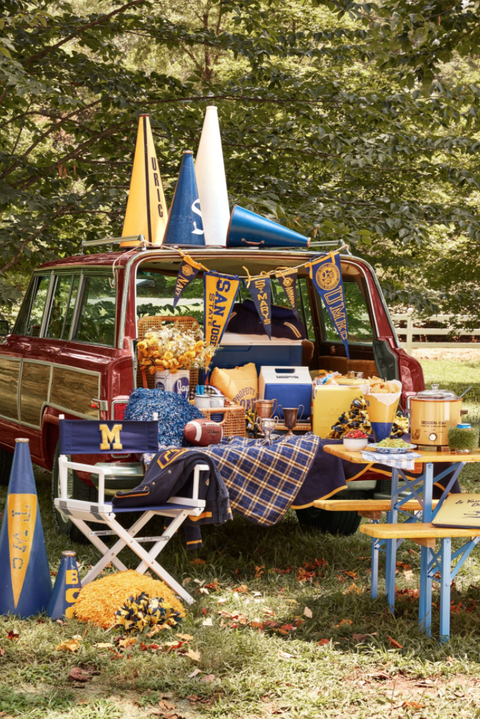 tailgate scene with a woody wagoneer and blue and yellow decorations