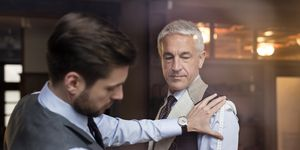Tailor fitting businessman for suit in menswear shop