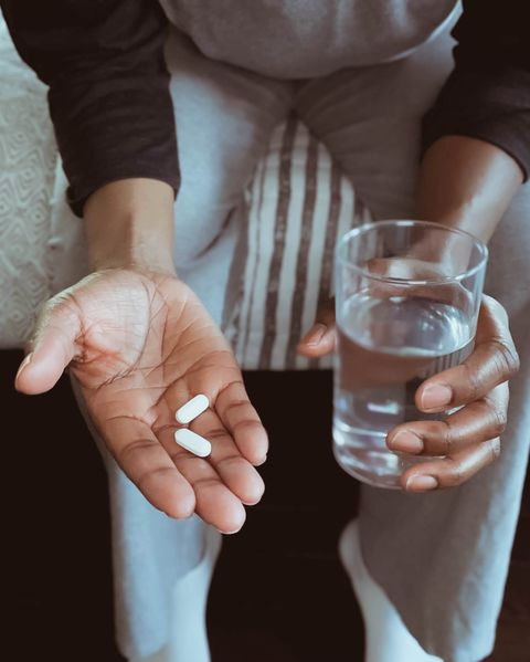 close up of woman sitting on edge of bed holding pills and glass of water
