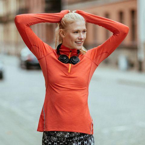 mujer rubia en la calle recogiéndose el pelo para correr