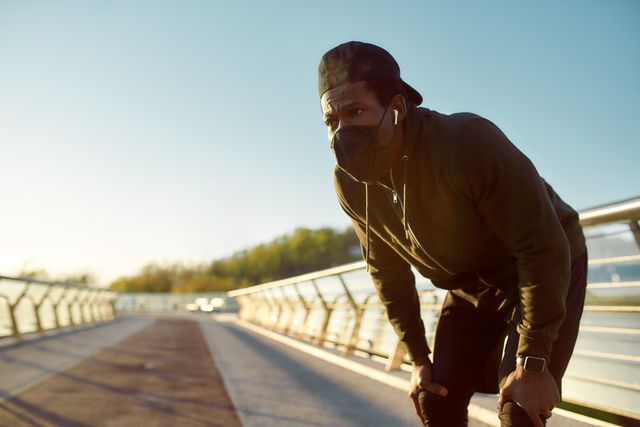 taking a break tired african jogger in protective mask resting after running while standing on the bridge in the morning running at sunrise sport during quarantine