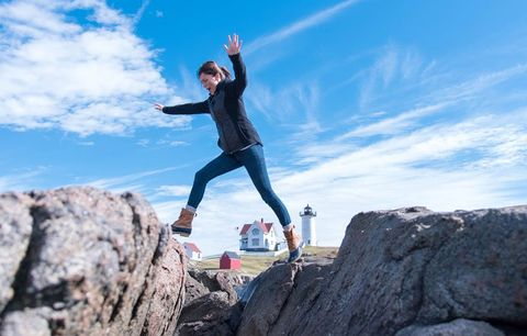 woman leaping between two large rocks