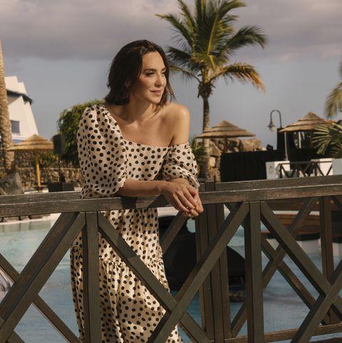 Tamara Falcó con un vestido asimétrico color crema con estampado en lunares, se apoya en la barandilla de la piscina de un resort.