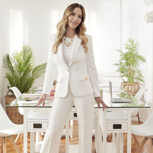 la influencer, con un traje pantalón en color blanco, posa ante su rincón de trabajo