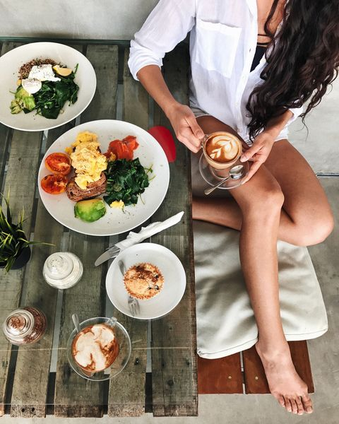 Tanned woman sitting and holding cup of aroma cappuccino in hands. Tasty muffin on wooden table for breakfast