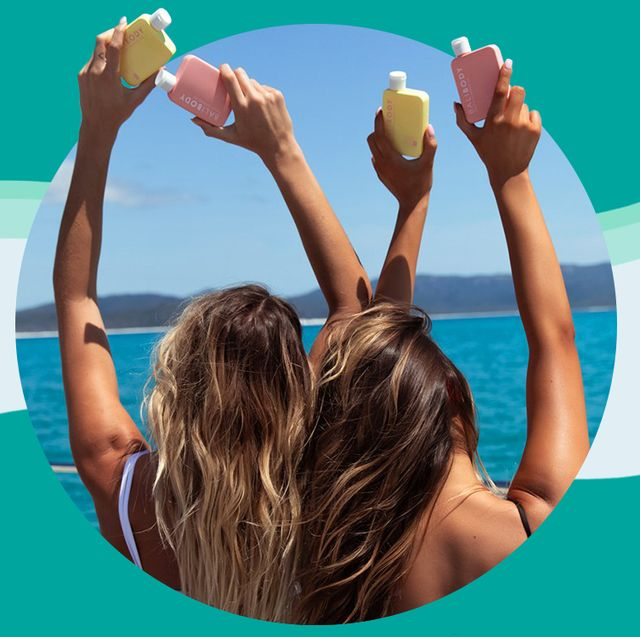 2 women holding up bali body tanning oil in front of ocean