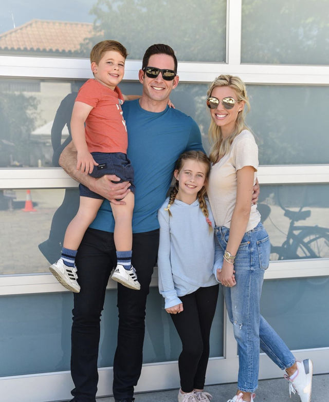 tarek el moussa, his children, and heather rae young in front of their beach house