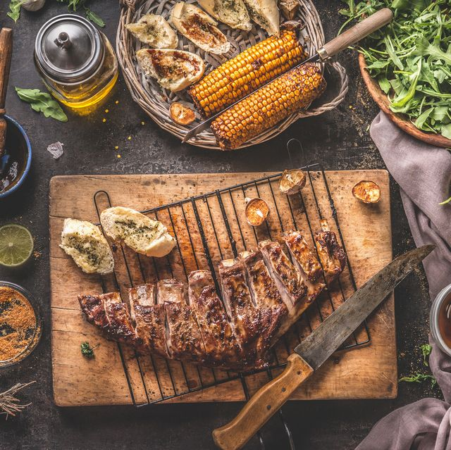 tasty grilled bbq meat ribs on wooden cutting board and grill grate with knife and fresh garlic herb butter bread served on rustic table with grilled corn cobs with bbq sauce , salad leaves and other tasty ingredients
