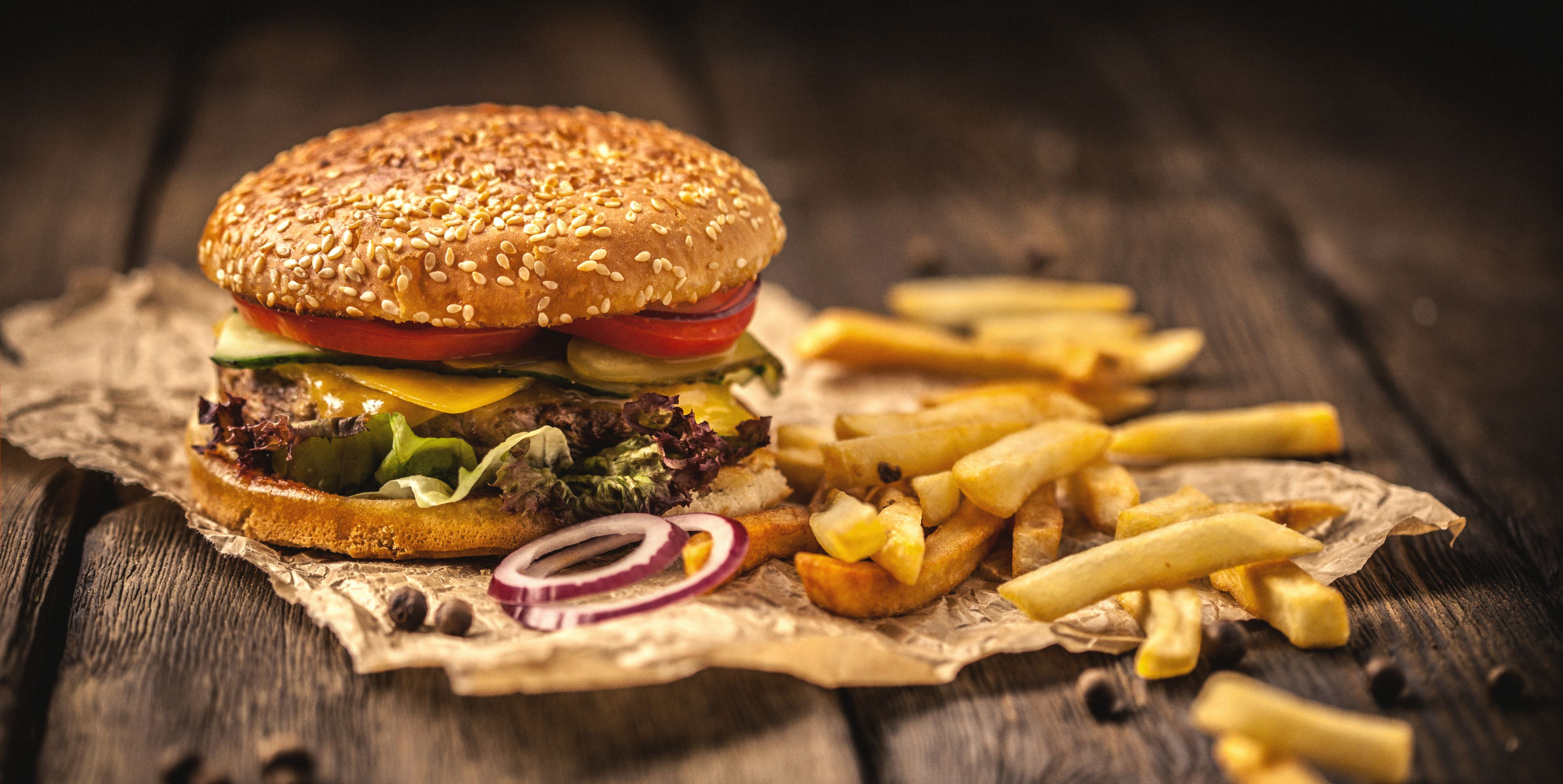 Tasty hamburger with french fries on wooden table