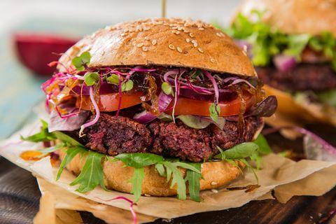 Tasty vegetarian beet burgers on wooden table