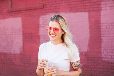 vrouw met tatoeage op haar arm drinkt sapje