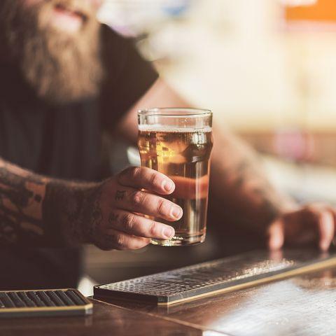 Tattooed bartender with beard working in pub