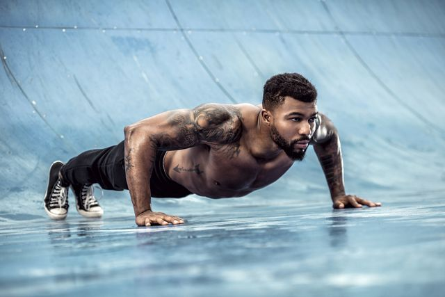 tattooed physical athlete doing pushups on sports field