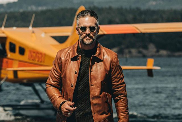 ma wearing leather jacket in front of a lake with a waterplane