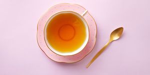 Tea cup on pastel pink background. Top view