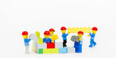 team of workman lego mini figure build a wall